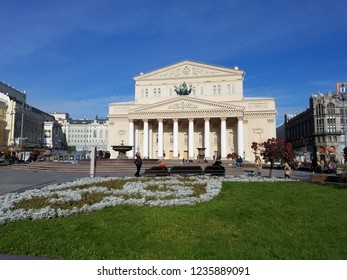 Bolshoi Theater of Moscow in daytime. Green lawn, clear sky.