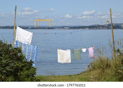 Bolshoy Kamen, Primorsky krai/Russia - 08.16.2020:  wet linen on rope against the Japanese sea, city Bolshoy Kamen, Zvezda shipyard and  Zvezda crane. Hangan Peninsula.bay with polluted water.