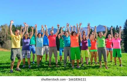 Bolsterlang, Bavaria, Germany, 10-19-2914, a big group of people with colorful clothes jubilating with hands up in beautiful landscape