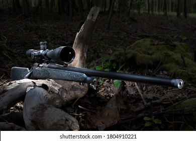 Bolt action rifle with a high powered scope on in the woods at dusk with room for text