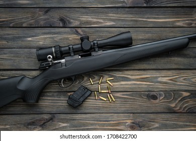 Bolt small caliber rifle 22lr with an optical sight on a wooden background. Hunting small-caliber weapon on a wooden table.