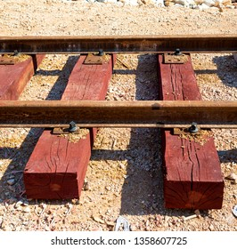 Bolted butt of rails and wooden sleepers laid on groundwork crushed stone. Railway industry and transport infrastructure