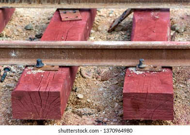 Bolted butt of rails and wooden sleepers laid on groundwork crushed stone. The sleepers have a red color because they have been impregnated with iron oxide