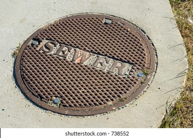 Bolted down sewer manhole cover in a sidewalk.
