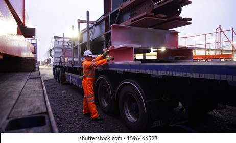 Bolton, Greater Manchester / UK Driver Wearing Full PPE and Chaining Down a Load of Steel Structures onto a Semi Truck Flat bed with Metal Posts Fitted.