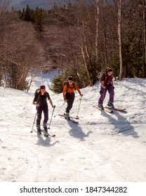 Bolton, Vermont, USA: April 3, 2017. Three women skinning uphill on backcountry skis in Bolton, Vermont