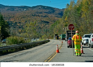 Bolton, VT, USA - October 9, 2013: A traffic control  worker stops traffic on Vermont  State Highway 2 during a paving project on a clear autumn day while cars stream by on the adjacent Interstate 89.