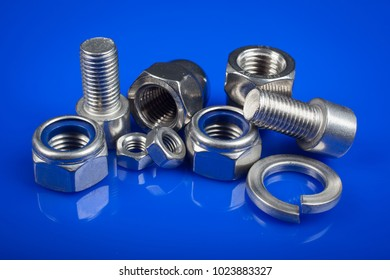 Bolts and nuts on blue background. Industry or construction concept