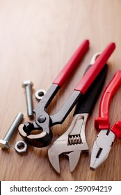 Bolts and nuts with pliers, adjustable wrench and a claw hammer on a wooden background