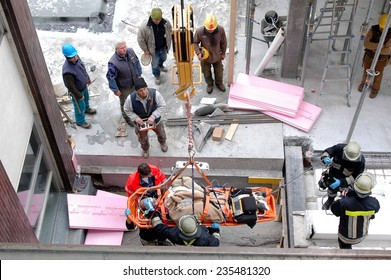 BOLZANO - ITALY, FEBRUARY 2, 2014: Firefighters and paramedics rescue a construction worker after crash. Male worker lying on the floor outside areal of a building site in Bolzano in February 2, 2014