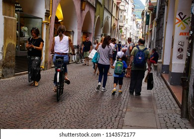 BOLZANO, ITALY - JUL 26, 2018 - Bicyclist on  the narrow cobbled street of Bolzano, Italy