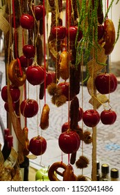 BOLZANO, ITALY - JUL 26, 2018 - Hanging apples, pretzels and sausages in the shop of Bolzano, Italy