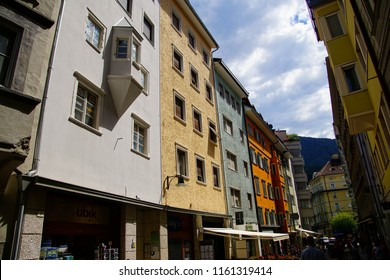 BOLZANO, ITALY - JUL 26, 2018 - Pastel buildings on arcaded street of Bolzano, Italy