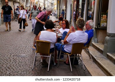BOLZANO, ITALY - JUL 26, 2018 - People relax at outdoor cafe in old city of Bolzano, Italy
