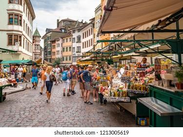 BOLZANO, ITALY - JULY 17, 2018: People shopping at a market on Piazza delle Erbe (Market Square in Italian), in the historic city center of Bolzano