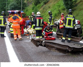 BOLZANO, ITALY - July 18, 2013: Paramedics Firefighters and police man working after a huge car crash collision. Car accident on the road with injured motorist on the Highway A22 on July 18, 2013.