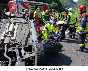 BOLZANO, ITALY - MAY 18, 2014: paramedics and firefighters working after a huge crash accident with overturned car on the Highway A22 on May 14, 2014