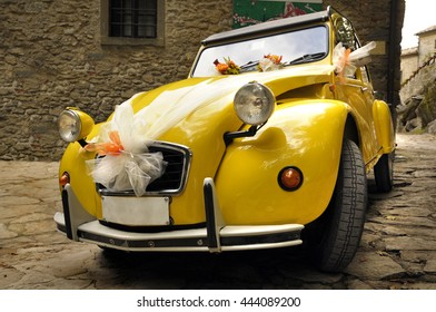 BOLZANO, ITALY - OCTOBER 13, 2012: Yellow Citroen 2CV decorated for a Wedding party. This car is very used for celebrations for its vintage look.