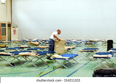 BOLZANO, ITALY - SEPTEMBER 5, 2015: A general view of the emergency camp where thousands of immigrants. Volunteers prepare blankets for refugees inside a gymnasium on September 5, 2015
