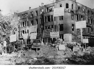 Bombed-out building in Wittenberg Platz, Berlin. Many of the signs posted give directions to merchants' new locations. Photo was taken by Danish photographer Hans Martin Herloff, Ca. March 1945.