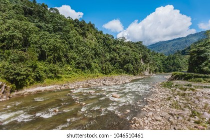Bomdila, Arunachal Pradesh, India. Kameng river flowing through forested valley of Himalaya foothills under bright clouded sky near Bomdila, Arunachal Pradesh, India.