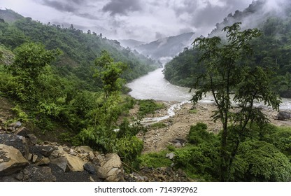 Bomdila, Arunachal Pradesh, India. The Kameng river flanked by forested slopes and boulders on a misty monsoon day as veiwed from National Highway 13 near Bomdila, Arunachal Pradesh, India.