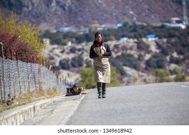 Bome County, Tibet, China. November 9, 2015: Tibetan prostration. Dressed in thick aprons and heavy mittens, a Tibetan couple making their arduous month-long journey to Lhasa.