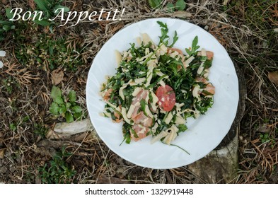 Bon appetite! Fresh salmon, cheese, cherry tomatoes and arugula salad on white plate on the ground, delicious food outdoor scene