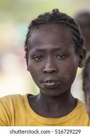 BONATA VILLAGE, OMO VALLEY. ETHIOPIA - JANUARY 2, 2014: Unidentified girl from Ari tribe at local village market.