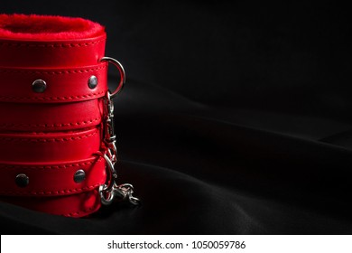 Bondage, adult sex games and BDSM lifestyle concept with close up on a pair of red leather handcuffs on black silk with copy space