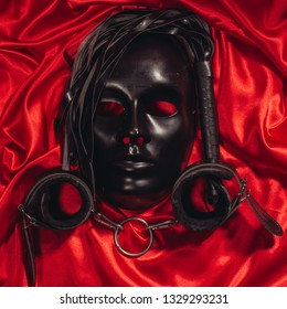 Bondage, kinky adult sex games, kink and BDSM lifestyle concept with a mask, pair of leather handcuffs, flogger, ball gag and a coller with a leash attached on red silk with copy space