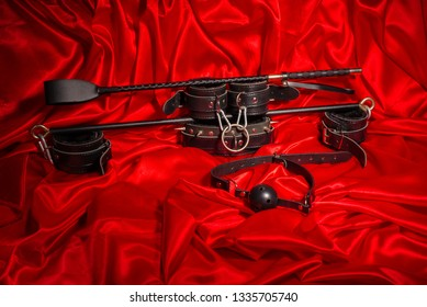 Bondage, kinky adult sex games, kink and BDSM lifestyle concept with a pair of leather handcuffs, flogger, ball gag and a coller with a leash attached on red silk with copy space