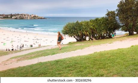 BONDI BEACH, SYDNEY, AUSTRALIA - DECEMBER 10, 2014: Young attractive girl walking down through Bondi park towards the famous Bondi beach in Sydney, Australia