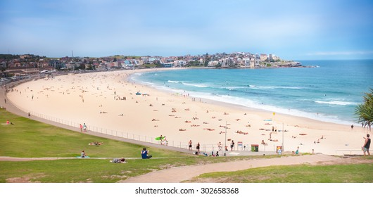 BONDI BEACH, SYDNEY, AUSTRALIA - DECEMBER 10, 2014: Famous Bondi Beach in Sydney on a beautiful sunny day, quiet clear sea with surfers and many sunbathing people on 1 km wide clean yellow sandy beach