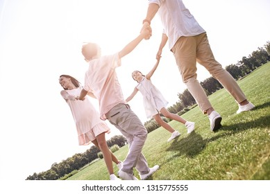 Bonding. Family of four holding hands dancing in circle on a gra