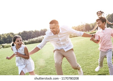 Bonding. Family of four running on grassy field playing playing touch and run game laughing cheerful