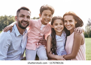 Bonding. Family of four standing on a grassy field hugging looking camera smiling cheerful close-up
