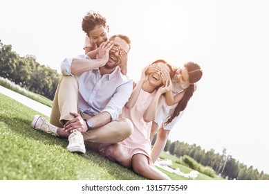 Bonding. Family og four sitting on a grassy field kids making su