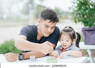 bonding time! Father and his child are playing at home.Cute little asian girl play math game with her dad, sitting on the table outdoor at backyard garden.Family holiday and togetherness.