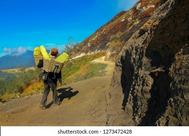 Bondowoso, East Java, Indonesia - November, 06, 2013 : A sulfur carrier seemed to be walking with a load on his shoulder. Sulfur basket reaches a load of 80kg