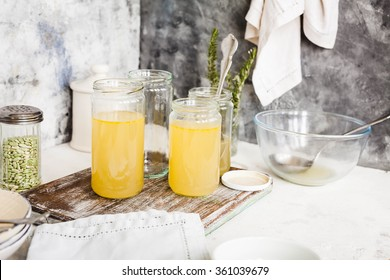 Bone broth soup in glass jar on a rustic cutting board. How to making base soup.