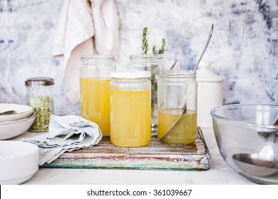 Bone broth soup in glass storage jars over  stone kitchen table. How to making base soup.