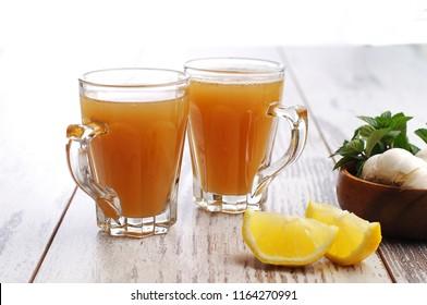 Bone broth in two glasses, lemon slices, garlic cloves, green herbs, white wooden background