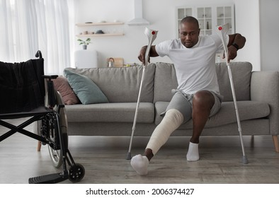 Bone fracture after incident, treatment at home, recovery. Black middle aged male with broken leg with plaster cast gets up from sofa with crutches in living room interior with wheelchair, empty space