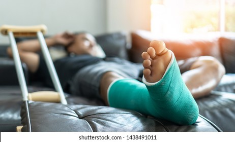 Bone fracture foot and leg on male patient with splint cast and crutches during surgery rehabilitation and orthopaedic recovery lying on couch staying at home