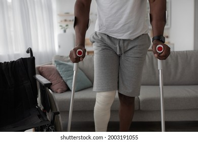 Bone fracture, injury, recovery and treatment at home after incident. Mature black man with broken leg with plaster of cast walk with crutches in living room interior with wheelchair, cropped