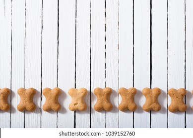 bone shape dog biscuits on white wood background