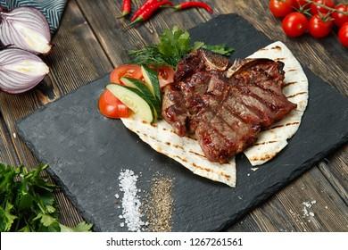 bone steak on stone panel