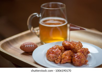 boneless buffalo hot wings on plate with glass beer mug and football decorations