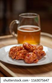boneless buffalo hot wings on plate with glass beer mug - soft focus